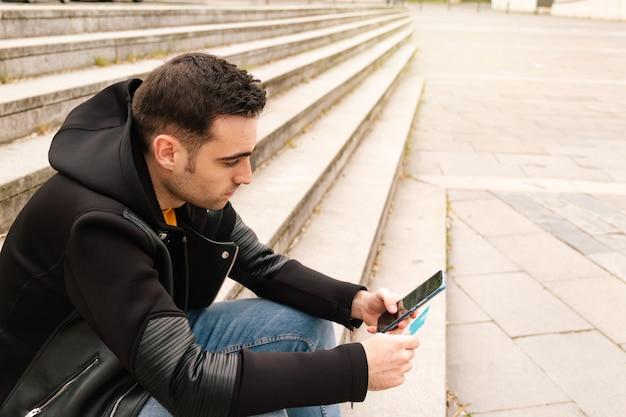Jeune homme tenant une carte de crédit lors d'un achat dans une boutique en ligne non physique. mode de vie futur et concept d'entreprise.