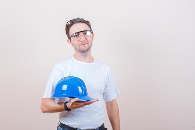 Jeune homme tenant un casque en t-shirt, jeans et à la gaieté