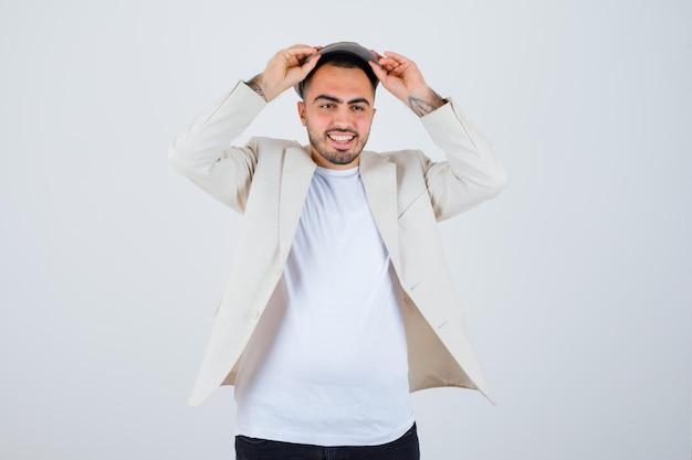 Jeune homme tenant une casquette à deux mains en t-shirt blanc, veste et casquette grise et l'air heureux