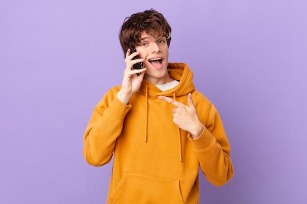 Jeune homme tenant une cellule à l'air excité et surpris en pointant sur le côté