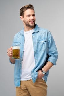 Jeune homme tenant une chemise de jeans tenant un verre de bière debout sur un mur gris.