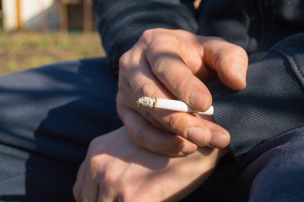 Un jeune homme tenant une cigarette à la main, assis à l'extérieur