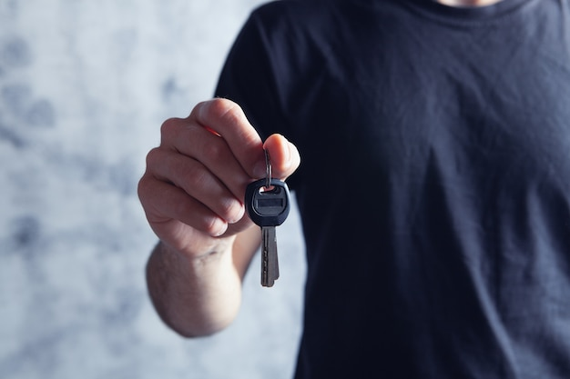 Jeune homme tenant les clés de la maison