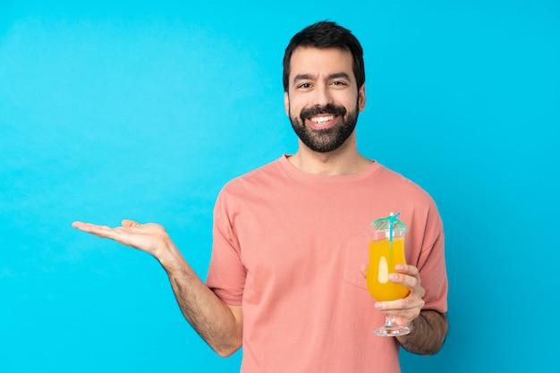 Jeune homme sur tenant un cocktail sur bleu tenant copyspace imaginaire sur la paume pour insérer une annonce