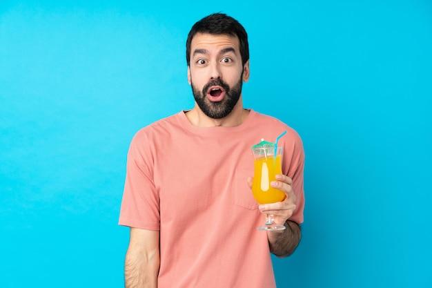 Jeune homme tenant un cocktail sur un mur bleu isolé avec une expression faciale surprise