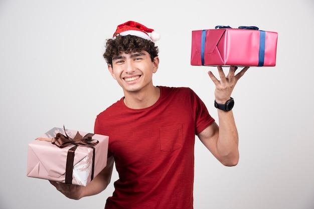 Jeune homme tenant des coffrets cadeaux avec le sourire.