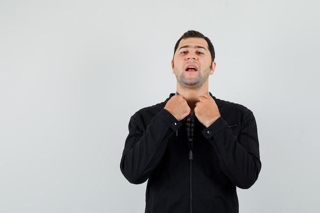 Jeune homme tenant le col de sa chemise en chemise, veste et à la fierté.