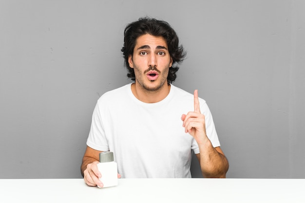 Jeune homme tenant une crème après-rasage ayant une excellente idée, concept de créativité.