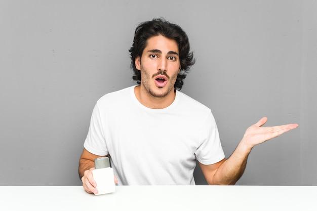 Jeune homme tenant une crème après-rasage impressionné tenant copie espace sur la paume.