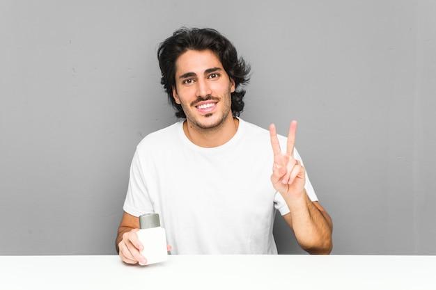 Jeune homme tenant une crème après-rasage montrant le numéro deux avec les doigts.