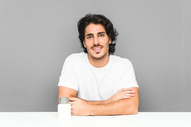Jeune homme tenant une crème après-rasage souriant confiant avec les bras croisés.
