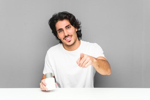 Jeune homme tenant une crème après-rasage sourires gais pointant vers l'avant.