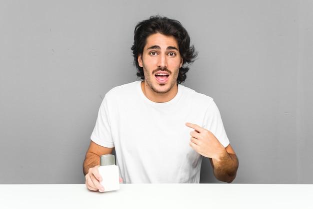 Un jeune homme tenant une crème après-rasage surpris se montrant du doigt, souriant largement.