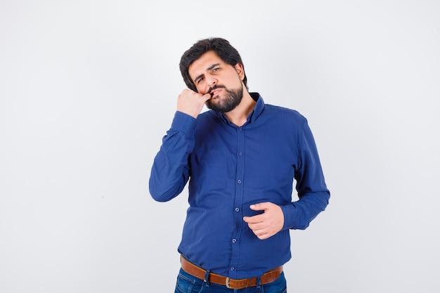 Jeune homme tenant le doigt dans la bouche en t-shirt rose et l'air pensif, vue de face.