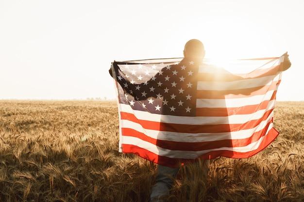 Jeune homme tenant le drapeau américain sur le dos en se tenant debout dans un champ de blé