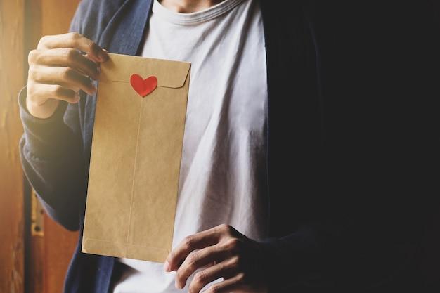 Jeune homme tenant une enveloppe brune décorée d'un coeur de symbole