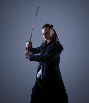 Jeune homme tenant une épée de samouraï. photo glamour.