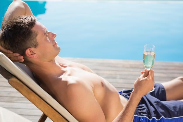 Jeune homme tenant une flûte de champagne au bord de la piscine