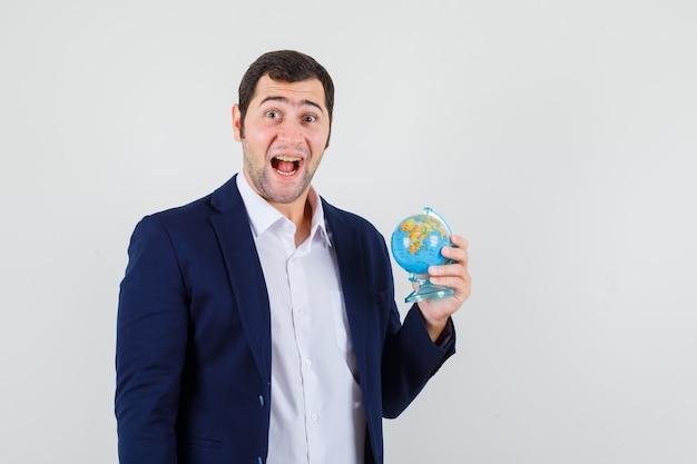 Jeune homme tenant le globe de l'école en chemise et veste et à la joie