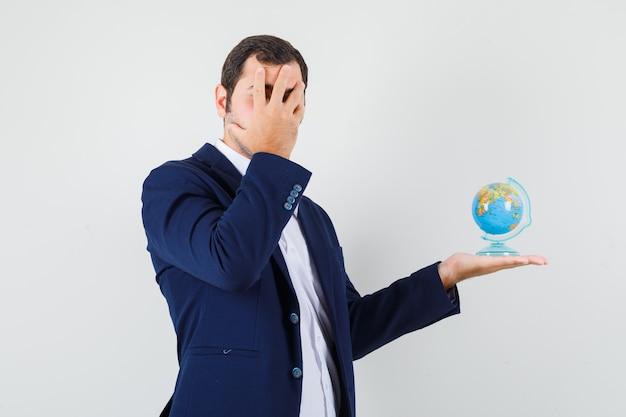 Jeune homme tenant le globe de l'école, couvrant le visage avec la main en chemise et veste