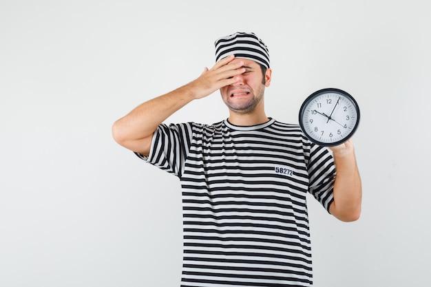 Jeune homme tenant une horloge murale en t-shirt, chapeau et à la recherche de tristesse. vue de face.