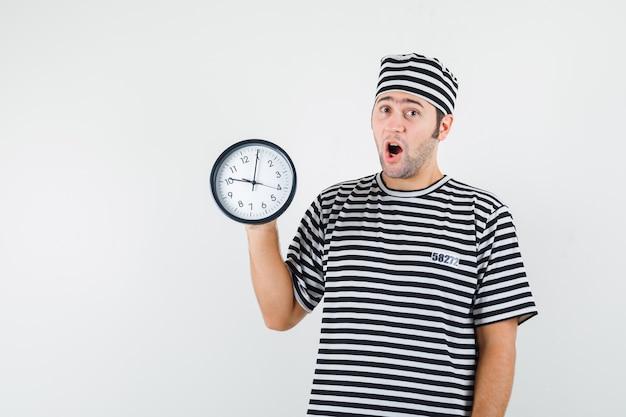 Jeune homme tenant une horloge murale en t-shirt, chapeau et regardant étonné, vue de face.