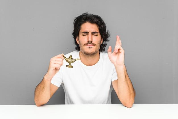 Jeune homme tenant une lampe magique croisant les doigts pour avoir de la chance