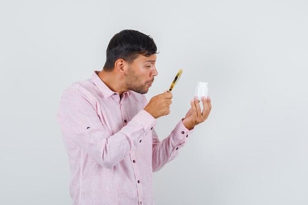 Jeune homme tenant la loupe sur la bouteille de pilules en vue de face de chemise rose.