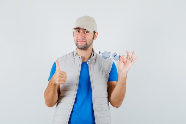 Jeune homme tenant des lunettes, montrant le pouce vers le haut en t-shirt, veste, casquette, vue de face.