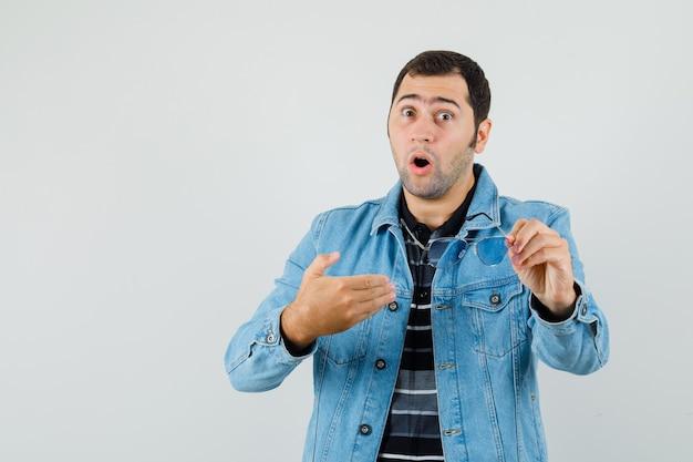 Jeune homme tenant des lunettes, se montrant en t-shirt, veste et à la surprise.