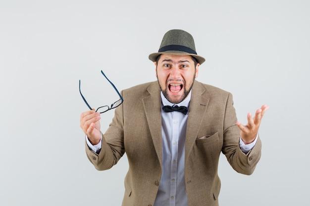Jeune homme tenant des lunettes tout en criant en costume, chapeau et à la fureur. vue de face.