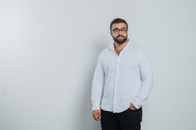 Jeune homme tenant la main dans la poche en chemise blanche, pantalon et beau