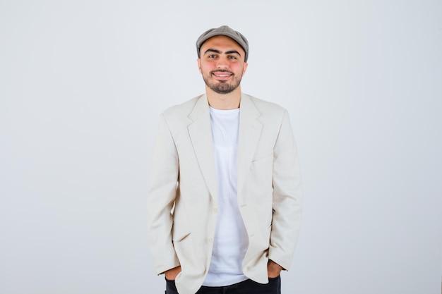 Jeune homme tenant la main dans la poche en t-shirt blanc, veste et casquette grise et l'air heureux