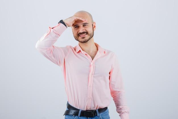 Jeune homme tenant la main sur le front en chemise, jeans et l'air joyeux. vue de face.