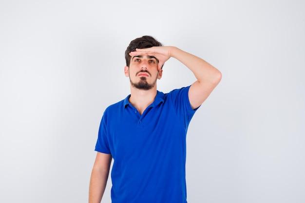 Jeune homme tenant la main sur le front, regardant loin en t-shirt bleu et ayant l'air sérieux