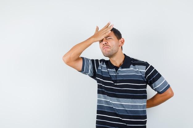 Jeune homme tenant la main sur le front en t-shirt et à la recherche de regret. vue de face.