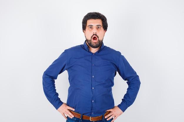 Jeune homme tenant la main sur la taille en chemise bleue et l'air surpris, vue de face.