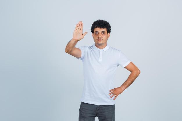 Jeune homme tenant la main sur la taille tout en montrant un panneau d'arrêt en t-shirt blanc et en jean et l'air sérieux, vue de face.