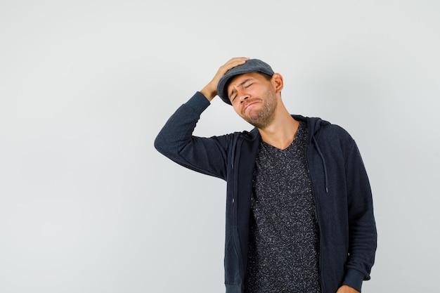 Jeune homme tenant la main sur la tête en t-shirt, veste, casquette et à regret, vue de face.