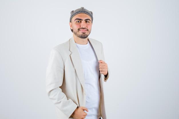 Jeune homme tenant la main sur la veste en t-shirt blanc, veste et casquette grise et l'air heureux