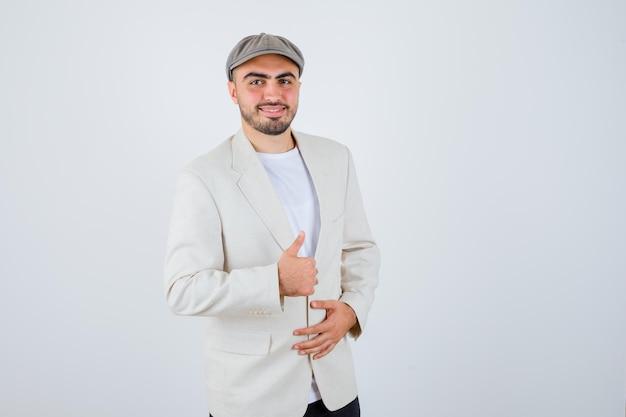 Jeune homme tenant la main sur la veste tout en montrant le pouce en t-shirt blanc, veste et casquette grise et l'air heureux