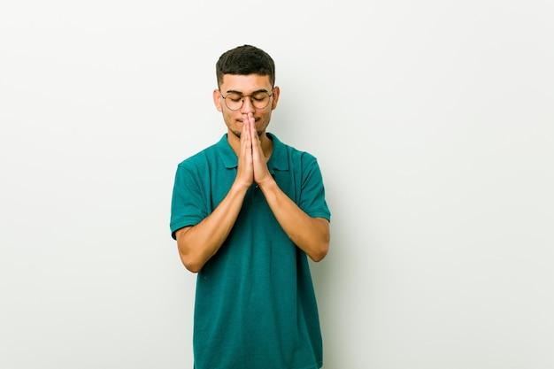 Jeune homme tenant les mains dans la prière près de la bouche, se sent confiant