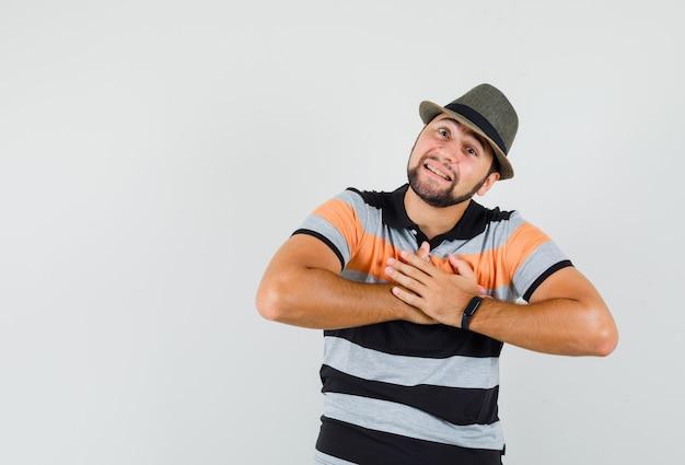 Jeune homme tenant les mains sur la poitrine en t-shirt, chapeau et à la reconnaissance, vue de face.