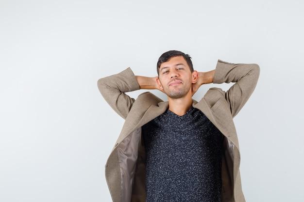Jeune homme tenant les mains sur son cou en veste marron grisâtre et à la vue de face, détendue.