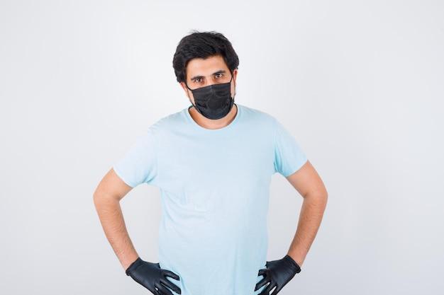 Jeune homme tenant les mains sur la taille en t-shirt et ayant l'air confiant. vue de face.