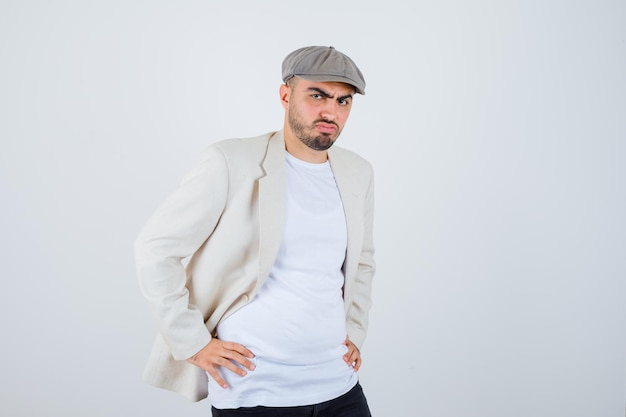 Jeune homme tenant les mains sur la taille en t-shirt blanc, veste et casquette grise et à la recherche de sérieux