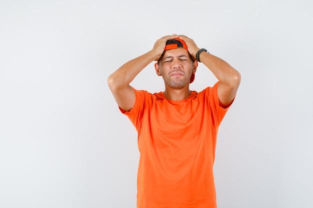 Jeune homme tenant les mains sur la tête en t-shirt orange et casquette et à regret