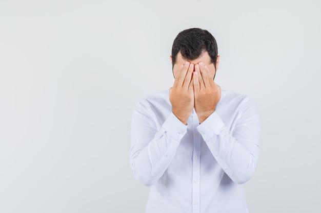 Jeune homme tenant les mains sur le visage en chemise blanche et à la gêne. vue de face.