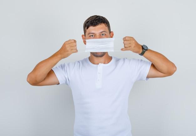 Jeune homme tenant un masque médical sur sa bouche en t-shirt blanc, vue de face.