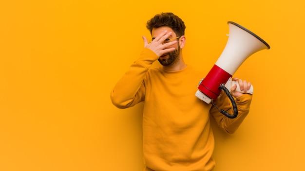 Jeune homme tenant un mégaphone embarrassé et riant en même temps